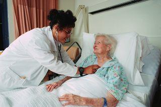 Older bed-ridden woman - Dr listening to heart
