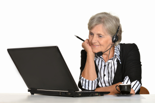 Older woman wotking with computer and headphones