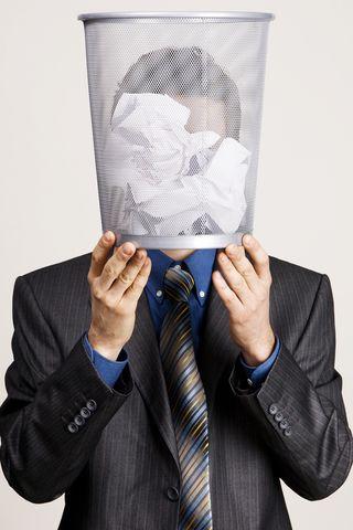 Man hiding behind trash basket