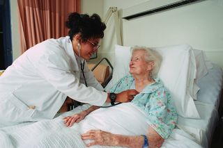 Older bed-ridden woman - Dr listening to heart