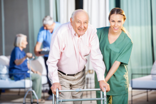 CNA helping elder man with walker