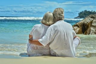 Retiree couple hugging on beach