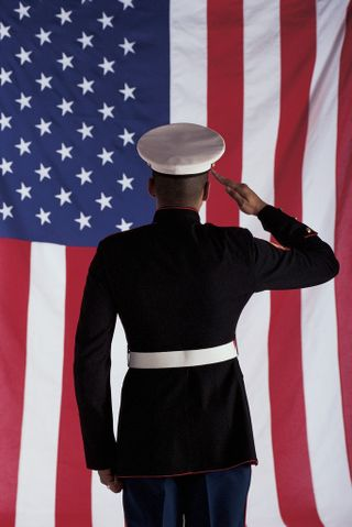 SOLIDER SALUTING A FLAG