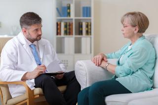Physchiatrist talking to elderly woman
